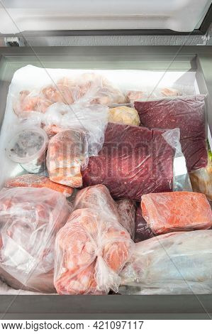 Frozen Food In The Freezer. Bagged Frozen Meat And Other Foods In A Horizontal Freezer. Food Preserv