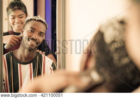 Barber Makes The Cut For Young Man In The Barbershop.  Close-up Of Professional Hairdresser Stylist