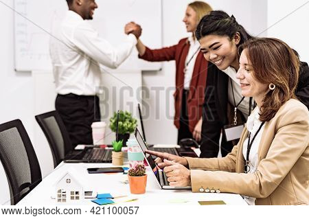 Group Of People, Making Plans Together, Two Females Looking  Screen Of Laptop. Real Estate Agents Wo