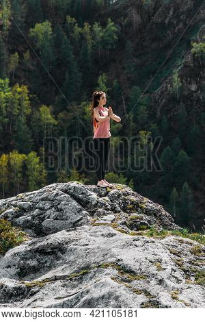 A Slender Woman Does Yoga Exercises Against An Incredible Backdrop Of Nature. The Woman Does Yoga In