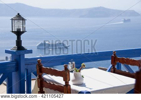 Panoramic View From A Terrace On The Sea Of Santorini With A Small Table Of A Tourist Restaurant On