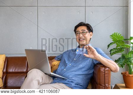 Senior Asian Man Sitting On Sofa Using Laptop Computer Holding Credit Card For Online Shopping And P