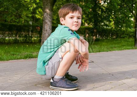 Boy With Dark Hair Squatting And Looks To The Side Thoughtfully. Child Is Squatting On The Sidewalk