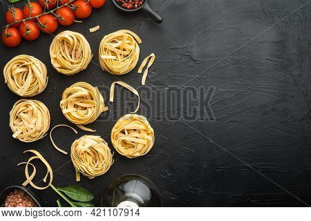 Rolled Tagliatelle Shape Of Italian Pasta With Ingredients Set, On Black Stone Background, Top View