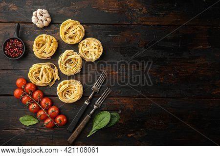 Ingredient Of Traditional Mediterranean Cuisine Uncooked Pasta Tagliatelle Set, On Old Dark  Wooden