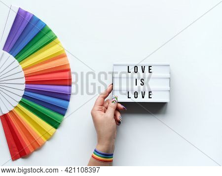 Lgbtq Pride Month Decor. Text Love Is Love On Lightbox. Rainbow Pattern Fan On Off White Background.
