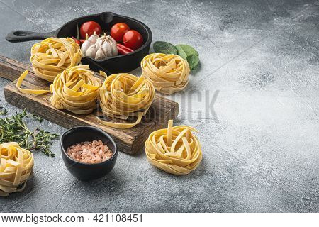 Ingredient Of Traditional Mediterranean Cuisine Uncooked Pasta Tagliatelle Set, On Gray Stone Backgr