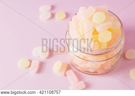 Chewing Sugary Citrus Gummy Candies In Glass Jar On Pastel Pink Background. Top View, Selective Focu