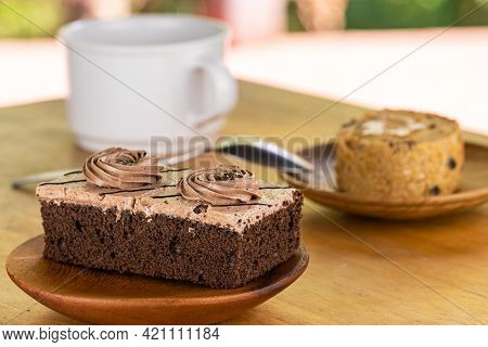 Mini Chocolate Cream Sponge Cake In Wooden Plate And Piece Of Prune Sponge Cake In Wooden Dish With