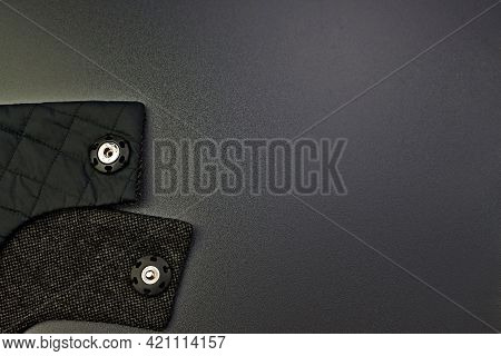 Close-up Of Woolen Fabric With Rivets On A Dark Gray Background . Accessories For Outerwear. Part Of