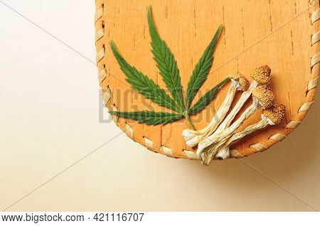 Dried Psilocybe Cubensis Psilocybin Mushrooms And Cannabis Leaf On Wooden Background, Flat Lay. Psyc