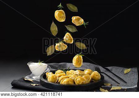 Dumplings On A Black Background On A Black Plate. Levitation Of Dumplings. Ready Meal.