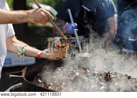 Chef Putting Delicious Boiled Mussels In Take Away Box, Cooking Seafood At Street Food Festival. Pre