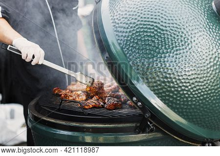 Chef Cooking Delicious Bbq Meat In Grill At Street Market In City. Vendor Roasting Tasty Smoked Stea