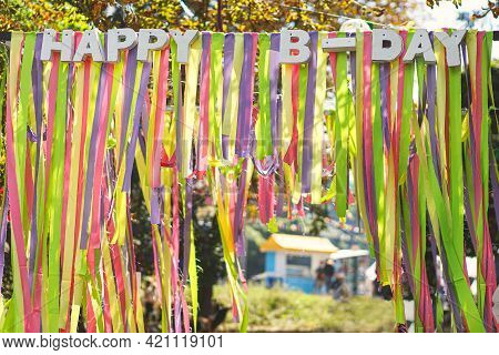 Beautiful Colorful Ribbons And Happy Birthday Words Hanging In Sunny Park At Street Food Festival, P
