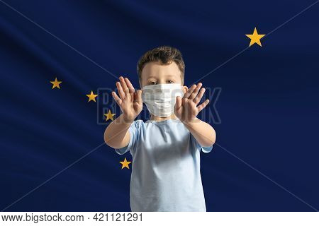 Little White Boy In A Protective Mask On The Background Of The Flag Of Alaska. Makes A Stop Sign Wit