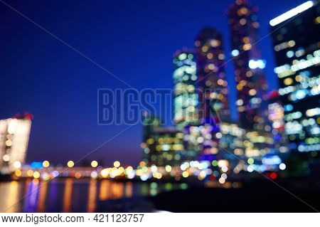 Night Bokeh Light In Big City. Defocused Illuminated Skyscrappers And River Of City Downtown. Abstra