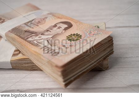 Stack Of Thai Baht Banknotes On Wooden Background, Business Saving Finance Investment Concept.
