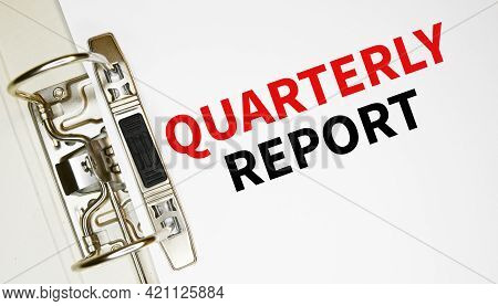 The Word Quarterly Report On A White Background With A Yellow Folder. Business Concept