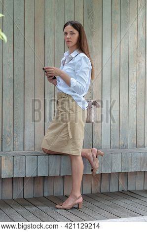 Portrait Of A Woman In A White Blouse. The Brunette Stands In The Park Against A Wooden Plank Wall