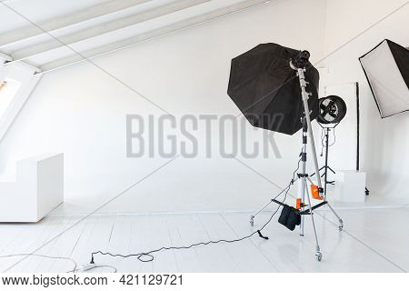 Empty Photo Studio With Lighting Equipment. Photographer Workplace Interior With Professional Tool S