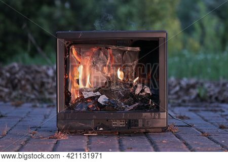 Burning fire in an old broken TV set, toxic air pollution from burning plastics of tube CRT television