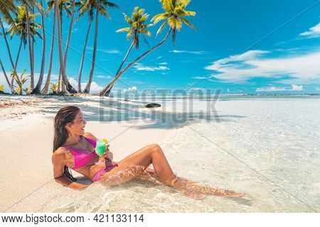 Beach vacation Asian bikini woman enjoying perfect summer holidays drinking blue hawaiian drink lying down sun tanning. Tahiti cruise island relaxing sipping cocktail on French Polynesia travel.