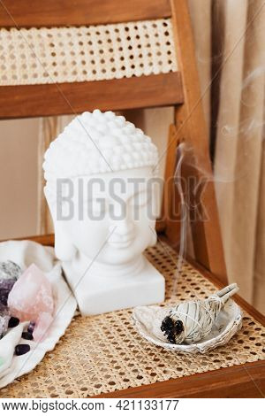 Buddha head statue by a burning sage smudge cleansing the house