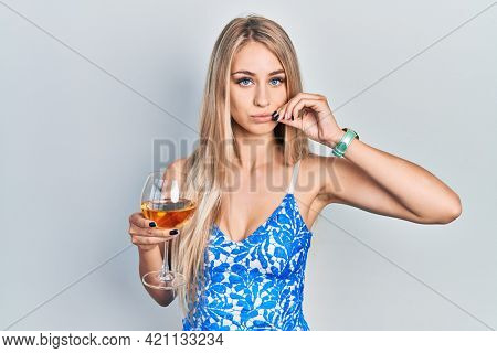 Young beautiful caucasian woman drinking a glass of white wine mouth and lips shut as zip with fingers. secret and silent, taboo talking