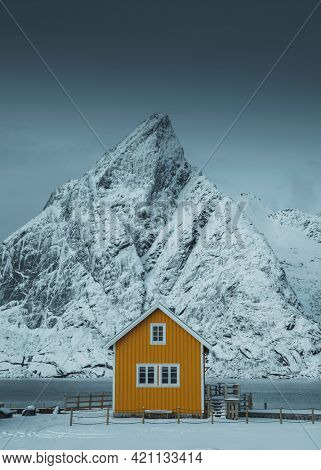 Yellow cabin framed by the snowy peak on Lofoten islands, Norway