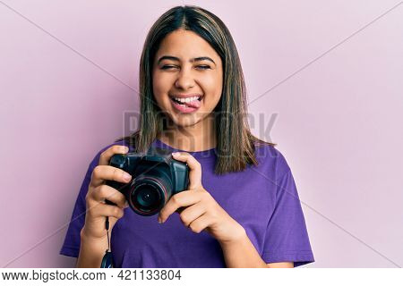 Young latin woman using reflex camera sticking tongue out happy with funny expression.