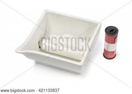 Vintage white porcelain photo developing bowl and a 120cm black and white roll film isolated on white background