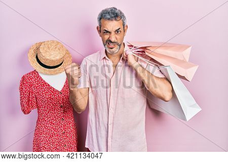 Handsome middle age man with grey hair holding shopping bags annoyed and frustrated shouting with anger, yelling crazy with anger and hand raised