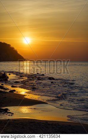 Majestic scenery of sandy beach and calm sea under orange sky with bright sun at sundown
