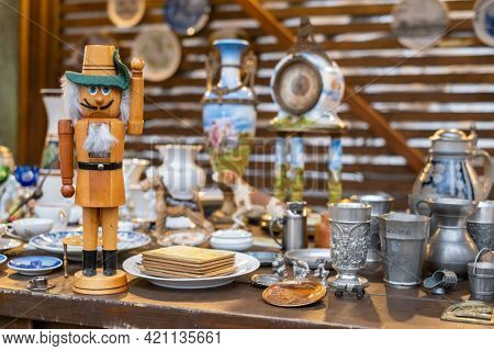 Creative handmade wooden doll placed on stall with various traditional souvenirs at local bazaar