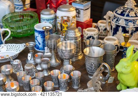 From above of various silver goblets and glasses placed on wooden counter at traditional souvenir market