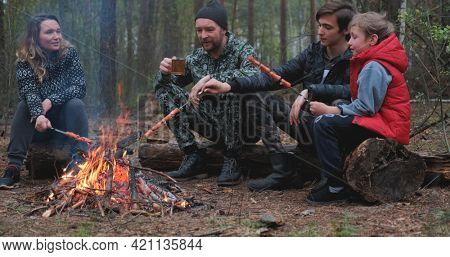 Family sits around a campfire on a summer evening. Children with parents are resting in the woods. Family frying sausages over a fire in the woods. Weekend in nature in good company.