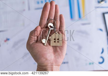 Key House And Wood House Shaped Keychain On Hand. Real Estate Agent Offer House. Concept For Buying