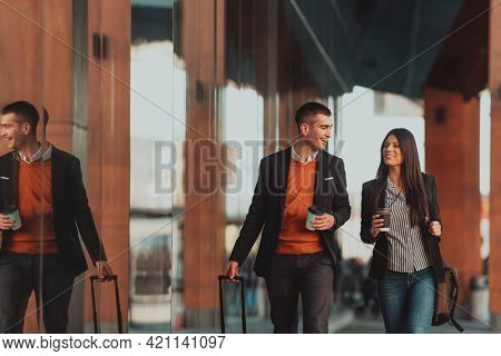 Business man and business woman talking and holding luggage traveling on a business trip