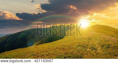 Mountain Landscape In Summer At Sunset. Grassy Meadows On The Hills Rolling In To The Distant Peak B