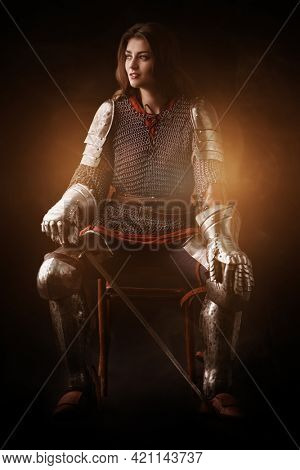 A beautiful noble warrior woman in chain mail and plate armor sits holding her sword. Medieval knight. Studio portrait on a black background.