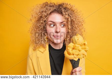 Surprised Curly Haired Woman Looks At Appetizing Ice Cream Feels Temptation To Eat High Calorie Dess