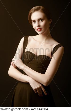 Beauty and makeup. A slender beautiful girl in a black tight-fitting dress on a black background. Evening fashion. Studio portrait.