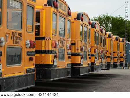 Many School Buses Parked At The Lot While Not Being Used On The Roadway.