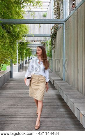 Portrait Of A Woman In A White Blouse. A Brunette Standing In The Park On The Planked Floor.