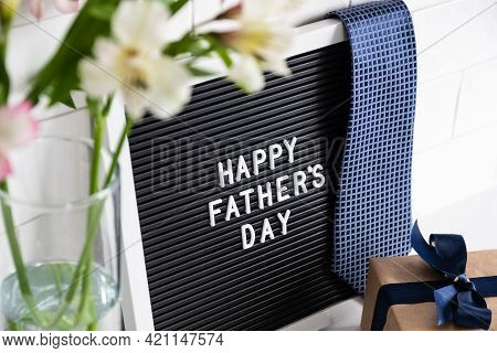Happy Fathers Day Concept. Letterboard With Sign Happy Father's Day, Gift Box, Flowers On Table.