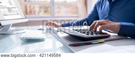 Financial Accounting. Man Using Calculator For Tax Invoice Calculation