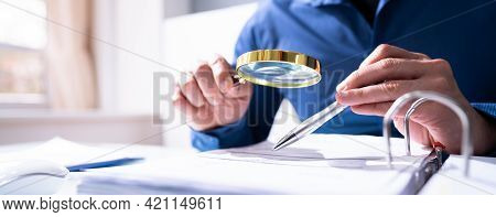 Auditor Or Fraud Investigator Looking At Tax Document Using Magnifying Glass