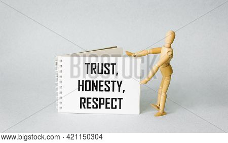Trust, Honesty, Respect - Words On A Notebook, Next To A Wooden Doll On A Blue Background