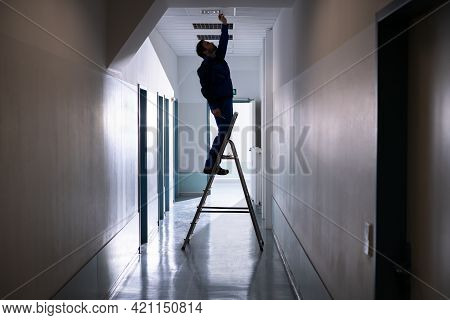 Technician Repairing Ceiling Fixture In Office On Stepladder